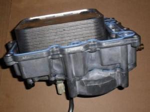 Una vez que los pernos se retiran, la tapa puede ser levantada de la parte superior del motor para exponer el refrigerador de aceite.