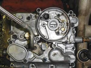 Esta es la parte superior del motor con la base del filtro de aceite eliminado. Retirar los tornillos exteriores de esta cubierta que sujetan a la parte superior del motor para tener acceso al refrigerador de aceite.